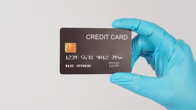 Cartão de crédito preto na mão com luva médica azul no fundo branco.