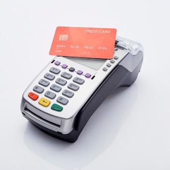 Cartão de crédito vermelho e terminal pos