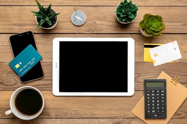 Cartão de débito do tablet para fazer compra, pedido, xícara de café, smartphone, suculentas na mesa de madeira