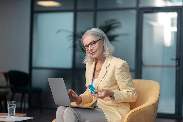 Cartão de débito. mulher caucasiana sênior elegante e bonita sentada em uma poltrona em um escritório moderno segurando um cartão de débito