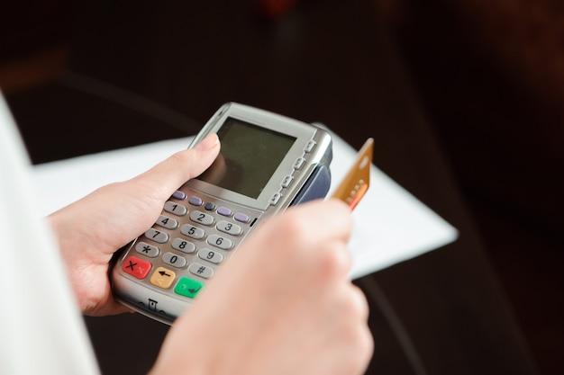 Cartão de débito swiping mão no terminal pos