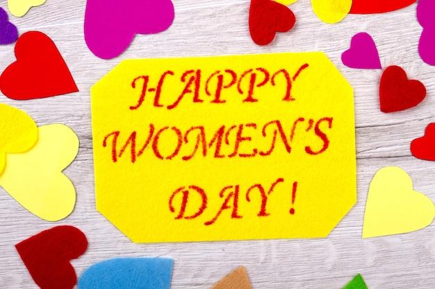 Cartão de dia da mulher e corações. corações de tecido perto de cartão postal amarelo. cores de alegria. prepare surpresa para senhoras.