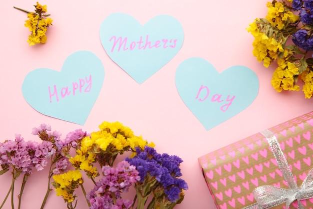 Cartão de dia das mães com flores e um presente. vista do topo