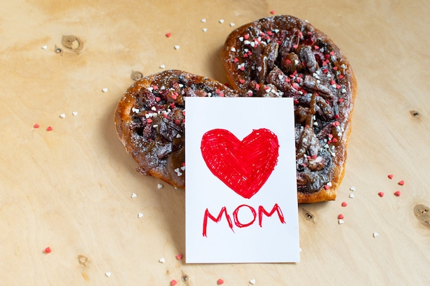 Cartão de dia das mães com um coração vermelho sobre um bolo em forma de coração de chocolate na mesa de madeira