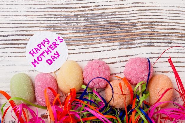 Cartão de dia das mães e doces saudando doces de papel e serpentina impressionam a mãe com doces caseiros