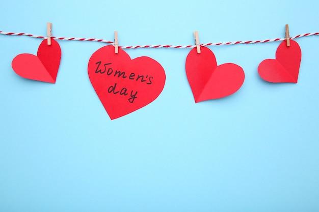 Cartão de dia das mulheres com corações em fundo azul.