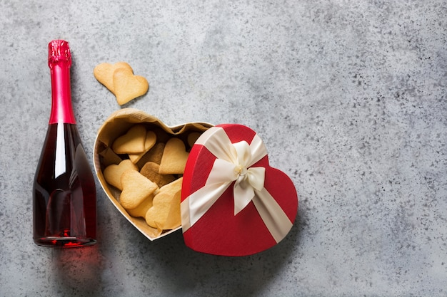Cartão de dia dos namorados. a garrafa do vinho espumante e os biscoitos no coração da caixa de presente deram forma no cinza. vista do topo.