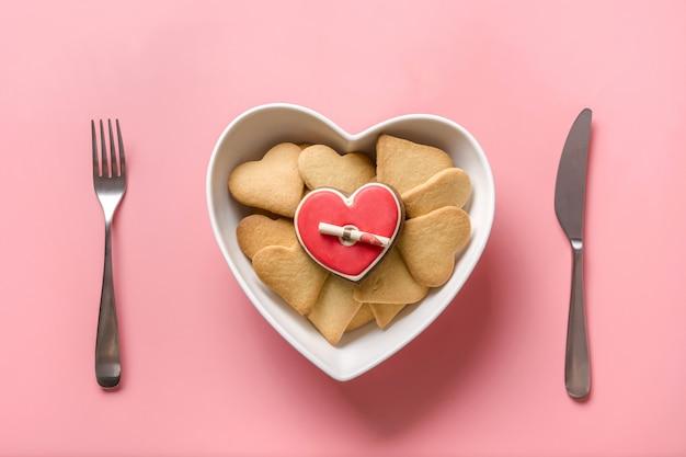 Cartão de dia dos namorados biscoitos com carta de amor em placa em forma de coração. configuração de mesa. conceito. vista de cima.