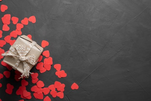Cartão de dia dos namorados. caixa com um presente sobre um fundo de pedra. corações vermelhos. copie o espaço. vista de cima. bandeira