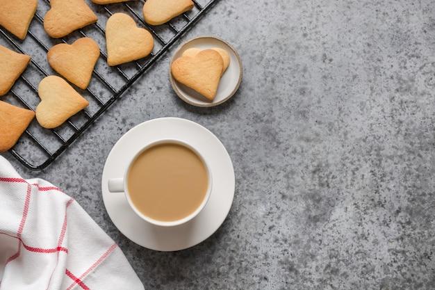 Cartão de dia dos namorados com biscoitos de coração e xícara de café na mesa de pedra cinza.