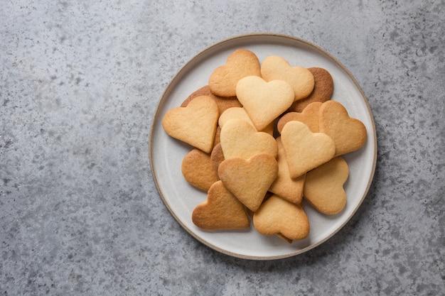 Cartão de dia dos namorados com biscoitos em forma de coração e xícara de café na mesa de pedra cinza.