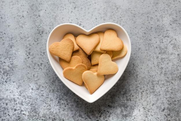 Cartão de dia dos namorados com biscoitos em forma de coração na mesa de pedra cinza.