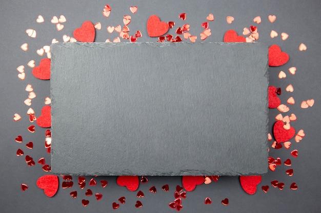 Cartão de dia dos namorados com confetes de corações vermelhos e lousa de ardósia preta no escuro.