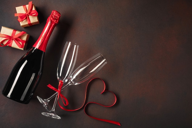 Cartão de dia dos namorados com copos de champanhe e caixas de presentes.