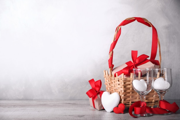 Cartão de dia dos namorados com corações, cálice e presentes na cesta na mesa de madeira. com saudações de espaço