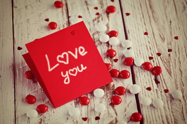 Cartão de dia dos namorados com corações pequenos e doces brancos vermelhos. imagem tonificada.