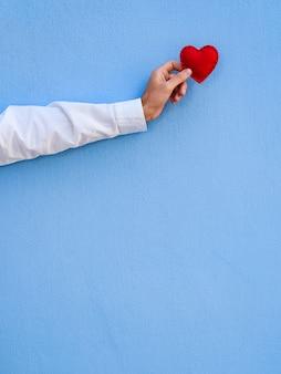 Cartão de dia dos namorados com espaço de cópia para o texto. o coração vermelho na mão do cara contra o fundo da parede azul