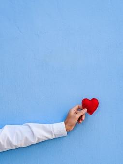 Cartão de dia dos namorados com espaço de cópia para o texto. o coração vermelho na mão do cara