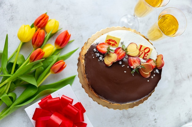 Cartão de dia dos namorados com flores de champanhe, caixa de presente e tulipas