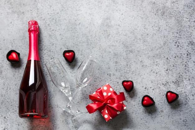 Cartão de dia dos namorados com garrafa de vinho espumante, caixa de presente, doces em forma de coração em cinza. conceito de namoro romântico. vista de cima.