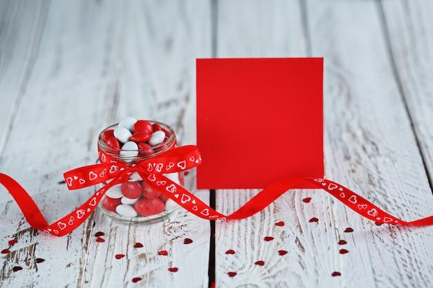 Cartão de dia dos namorados com pote de doces coloridos decorado com um laço vermelho