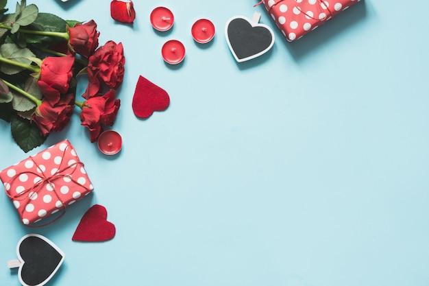 Cartão de dia dos namorados com presentes, corações vermelhos em fundo azul