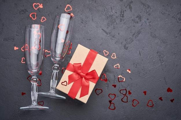 Cartão de dia dos namorados com taças de champanhe e caixa de presente com fita vermelha