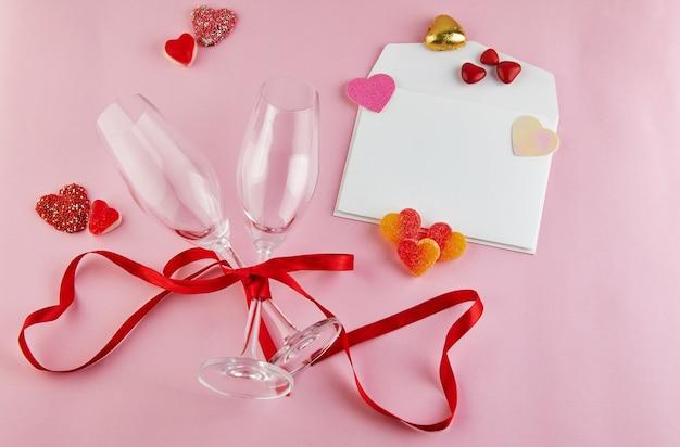 Cartão de dia dos namorados com taças de champanhe e corações de doces na mesa-de-rosa. topo