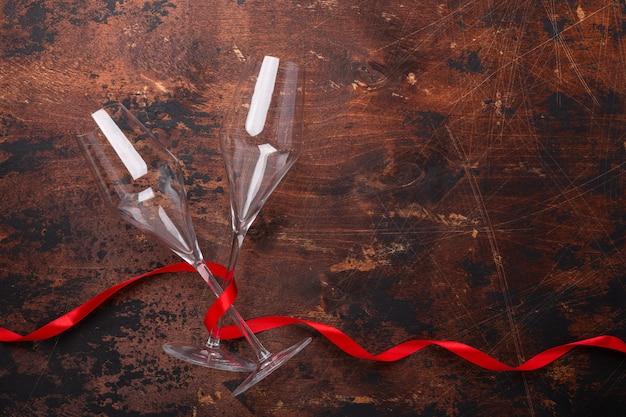 Cartão de dia dos namorados com taças de champanhe e fita vermelha em fundo de madeira