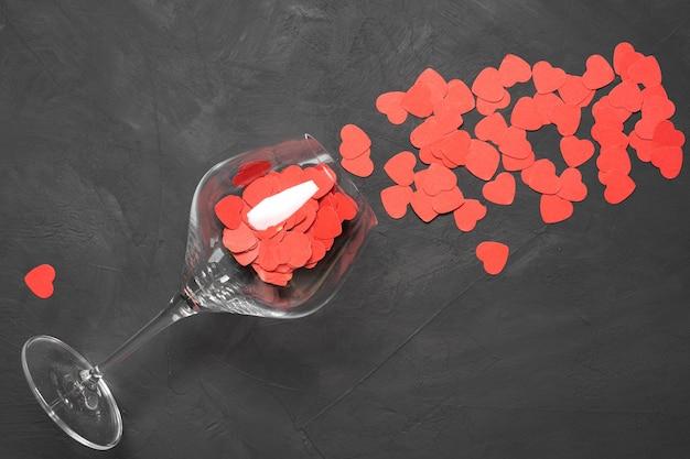 Cartão de dia dos namorados com taças de vinho e corações com fundo de pedra. vista superior com local para as suas saudações. flat la