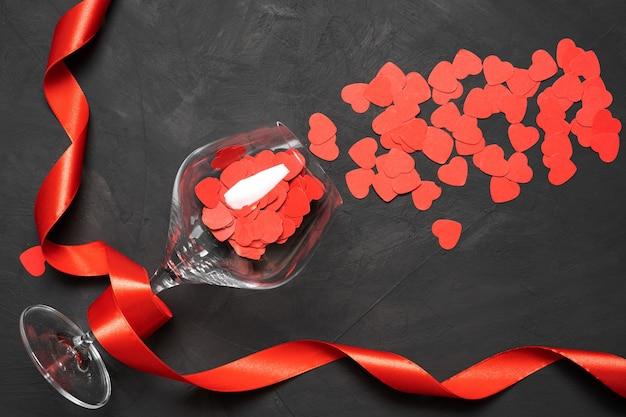Cartão de dia dos namorados com taças de vinho e corações em um fundo de pedra. copie a vista superior do espaço. flat la