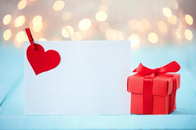Cartão de dia dos namorados com um coração vermelho e caixa de presente