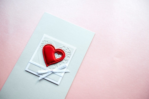 Cartão de dia dos namorados com um coração vermelho isolado em um fundo rosa claro