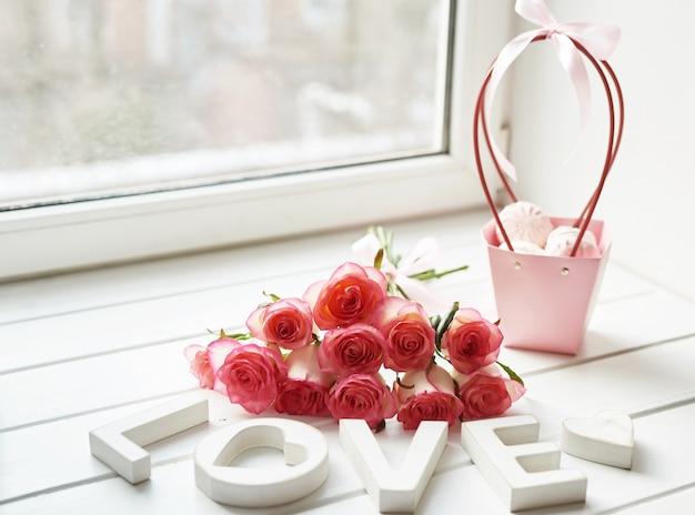 Cartão de dia dos namorados. composição com rosas frescas e molduras para fotos no peitoril da janela. espaço para texto. composição floral com inscrição amor. dia das mães e 8 de março cartão