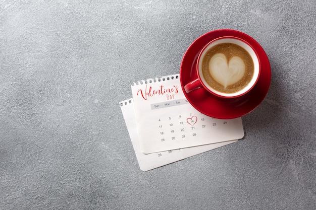 Cartão de dia dos namorados. copo de café vermelho sobre o calendário de fevereiro. vista do topo