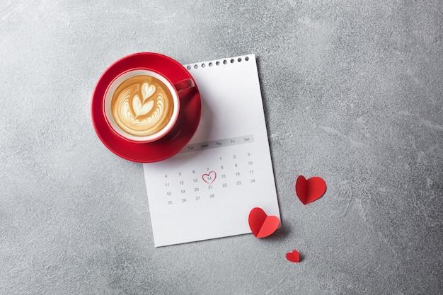 Cartão de dia dos namorados. copo e caixa de presente vermelhos de café sobre o calendário de fevereiro. vista do topo