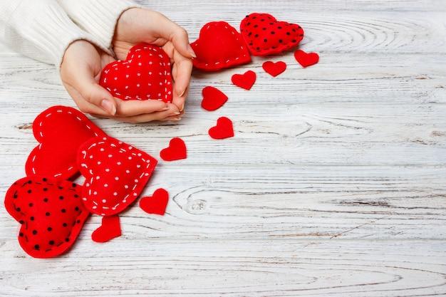 Cartão de dia dos namorados. corações artesanais na mesa de madeira. garota segurando um coração vermelho. vista superior com espaço para texto