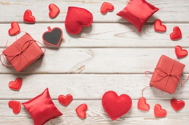 Cartão de dia dos namorados. decoração vermelha, corações, presentes na placa de madeira branca e copyspace. vista do topo.