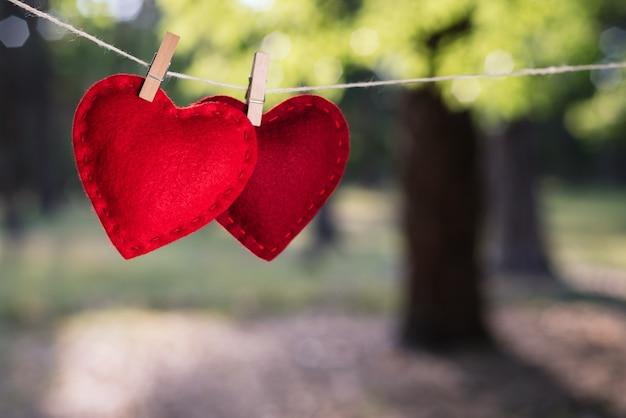 Cartão de dia dos namorados. dois corações vermelhos em um fundo desfocado no parque