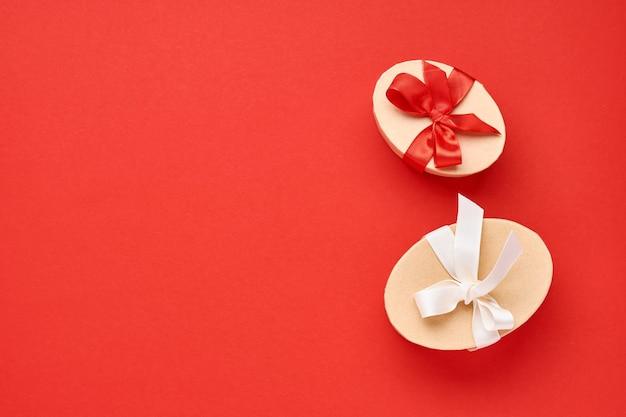 Cartão de dia dos namorados. duas caixas de presente com fita vermelha e estatuetas de coração em fundo vermelho vista superior com espaço de cópia.