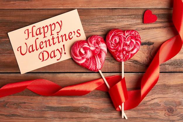 Cartão de dia dos namorados e fita. coração em tecido e bombons vermelhos. clima romântico para férias.