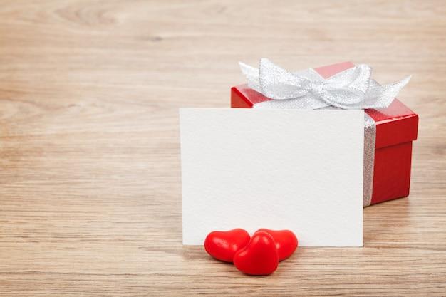 Cartão de dia dos namorados em branco, caixa de presente e corações de bombons vermelhos em fundo de madeira