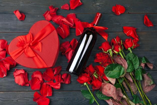 Cartão de dia dos namorados. flores de rosas vermelhas, vinho e caixa de presente na mesa de superfície de madeira.