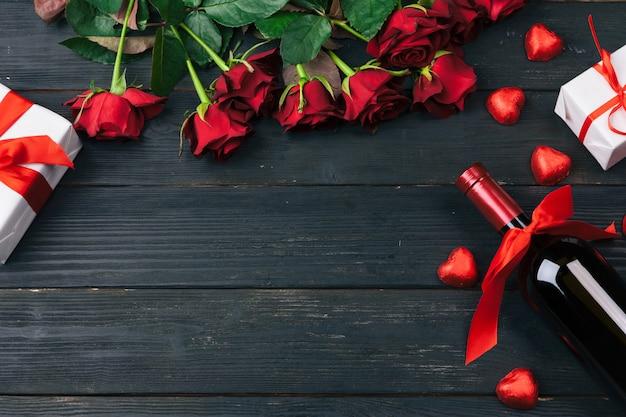 Cartão de dia dos namorados, flores rosas vermelhas, vinho e caixa de presente na mesa de madeira.