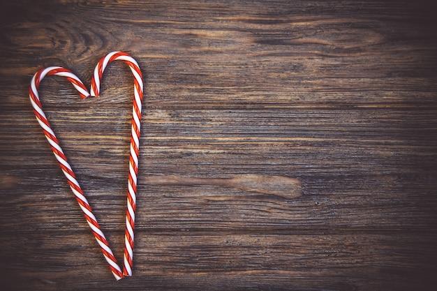 Cartão de dia dos namorados. forma de coração de cana doce na madeira rustik escuro