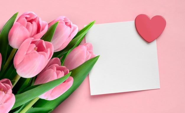 Cartão de dia dos namorados mãe com tulipas cor de rosa e nota de papel em branco com coração no fundo rosa.