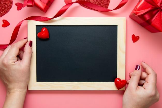 Cartão de dia dos namorados. mãos femininas sobre o quadro de quadro de giz. amor, fundo de caixa de presente rosa.
