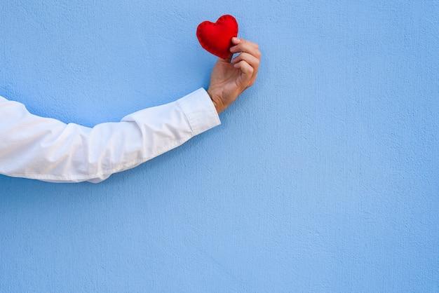 Cartão de dia dos namorados. o coração vermelho na mão do cara contra o fundo da parede azul. ð¡opy espaço para saudação ou texto publicitário