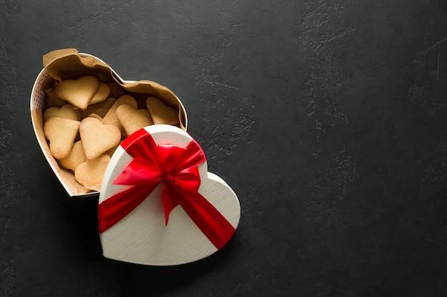 Cartão de dia dos namorados. os biscoitos de homamade no coração da caixa de presente deram forma no preto. vista do topo.