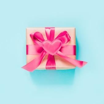 Cartão de dia dos namorados. presente com fita rosa e coração na superfície azul. vista do topo. imagem quadrada.